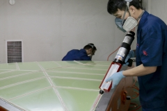 Workers apply the high performance adhesive
