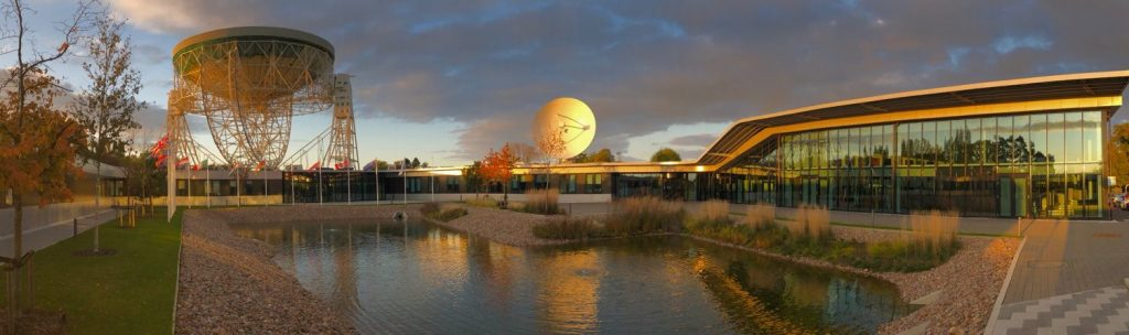 A panoramic image of SKA Global HQ with flags around the central pond, and the huge 76m Lovell Telescope in the background