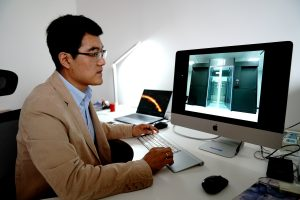 Prof. Tao An at his computer looking at an image of the SRC prototype.